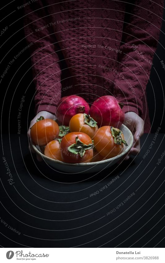 Plat of persimmon and pomegranates autumn biologic black background copy space dark delicious food fruits good hands healthy holding indoor many nutrition