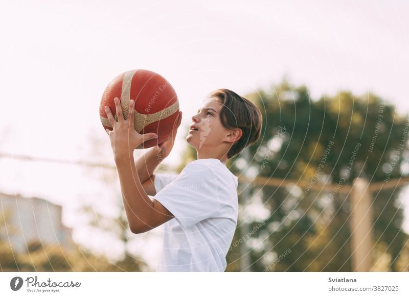 Close-up of a young athlete's hands holding a basketball. The athlete is preparing to throw. Sport, athlete throwing player boy healthy exercise athletic field
