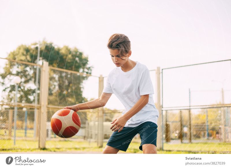 Focused cute boy athlete leads the ball in a game of basketball. A boy plays basketball after school. Sports, healthy lifestyle, leisure dribbling sport player