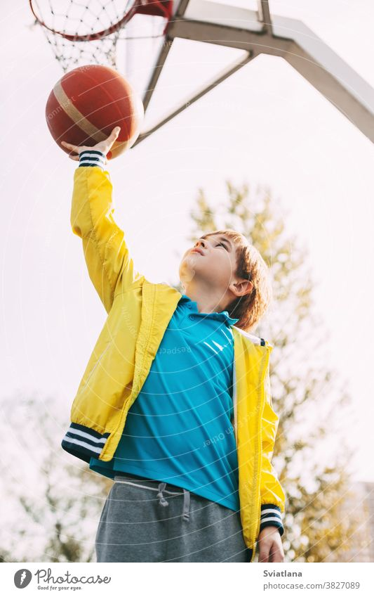 Portrait of a cute boy basketball player standing with a ball in his hands next to the basketball Hoop. The concept of sport and a healthy lifestyle game active
