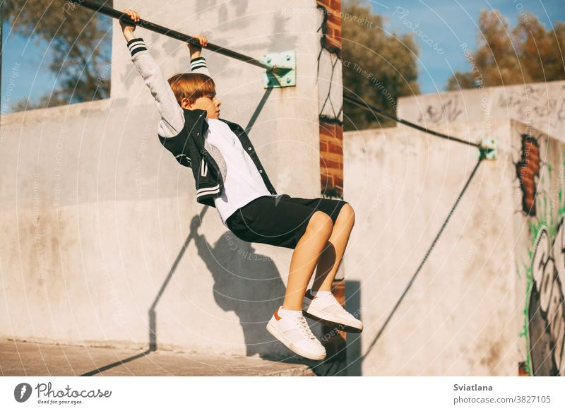 Cute boy holding hands on the horizontal bar in the Park. The boy is hanging at arm's length young sport healthy strong exercise male training athlete workout