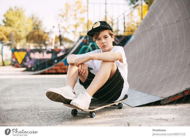 A beautiful teenager is sitting on a skateboard in a special area of the Park. A boy is resting after riding in a skatepark. Active rest in the fresh air kids