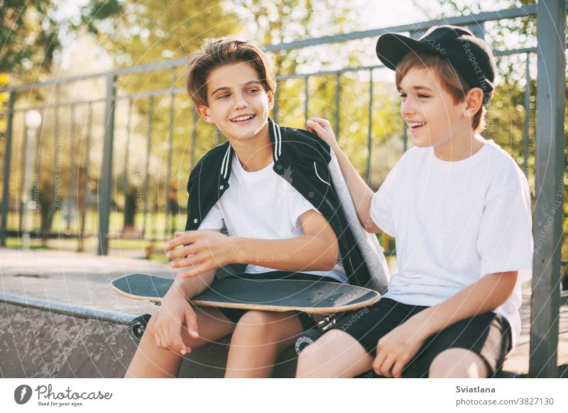 Two cute teenagers sit in a skatepark, relax after skateboarding and chat. Boys enjoy their free time in the skate Park, sitting on the ramp. The concept of youth, unity and friendship