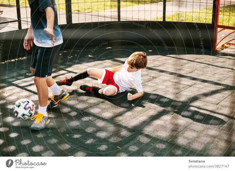 Boys play soccer on the freestyle soccer field. Boys fight for the ball in the game. Sport, game, competition, football freestyle player playing boy two