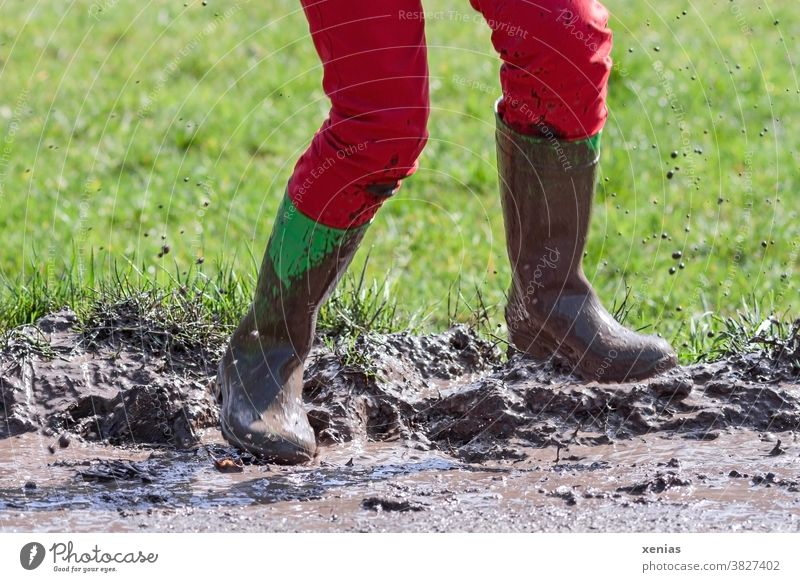 Legs in red trousers and green rubber boots jumping in a muddy puddle, so that the mud flies up Puddle slush Rubber boots Jump Muding Flying Inject Boots Joy