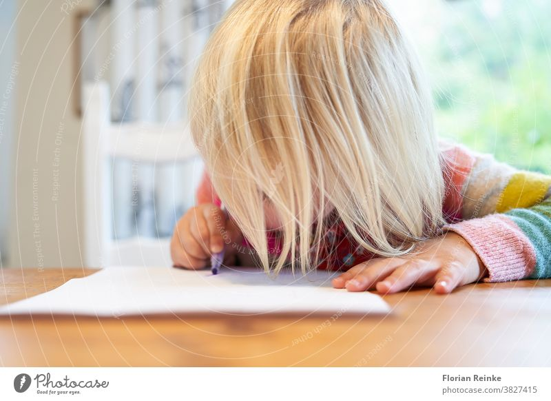4 year old blonde girl with a brightly colored striped sweater sits at a wooden table and draws with a purple pencil on a piece of white paper child's hand