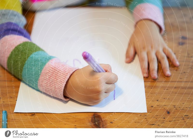 4 year old blonde girl with a brightly colored striped sweater sits at a wooden table and draws with a purple pencil on a piece of white paper