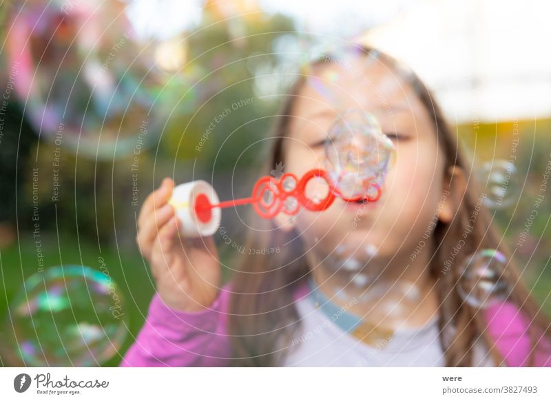 A little girl makes soap bubbles in the garden caucasian child childhood floating flying. burst fragile fun human playing shimmering tender toddler toddlerhood
