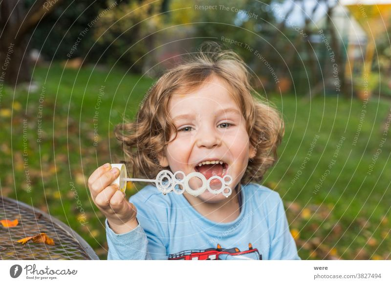 A little boy makes soap bubbles in the garden caucasian child childhood floating flying. burst fragile fun human playing shimmering tender toddler toddlerhood