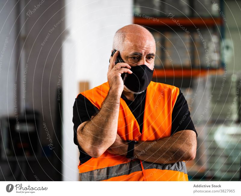 Concentrated male warehouse worker talking on smartphone man conversation phone call serious manager at work workplace protect occupation mask storehouse