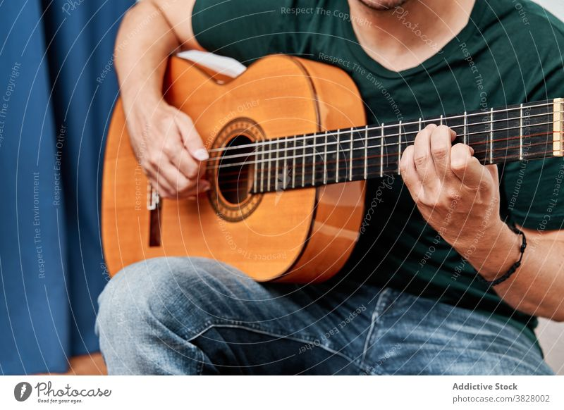 Anonymous musician playing guitar sitting on chair at home man acoustic hipster flat musical instrument denim classic practice melody guitarist banjo casual