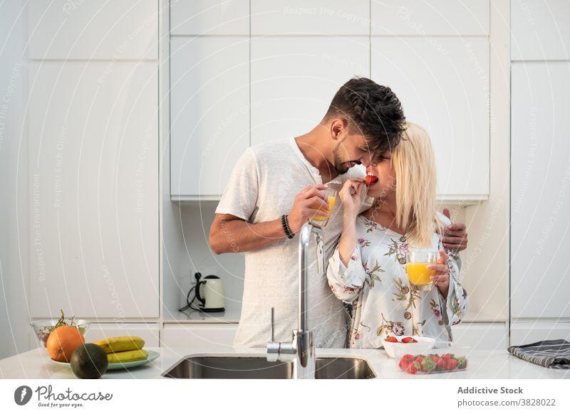 Loving couple having breakfast in modern kitchen together strawberry eat enjoy morning hug love early fresh orange juice food fruit home relationship drink
