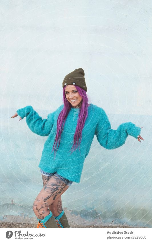 Stylish tattooed woman on street style informal pink hair appearance eccentric fancy trendy shabby building urban area outfit relax town cool millennial grunge