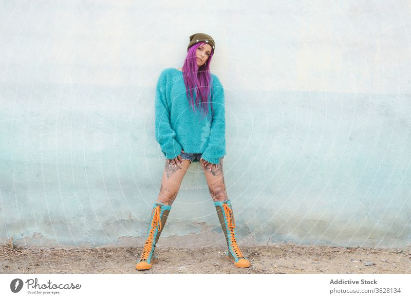 Stylish tattooed woman on street style informal pink hair appearance eccentric fancy trendy female shabby building urban area outfit relax town cool millennial