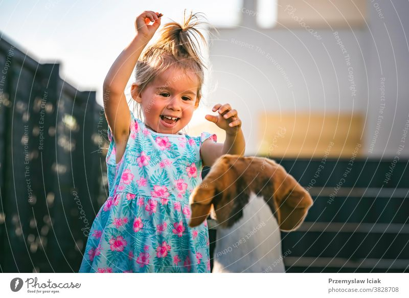 Baby girl running with beagle dog in backyard in summer day. Domestic animal with children concept. baby togetherness 2-3 family treat chase love person kid