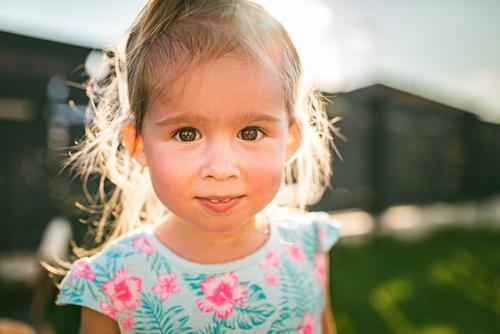 Beautiful baby girl portrait in sunny, green yard in summer. childhood background 2-3 happines adorable cute nature laughing fun emotions smile sweet