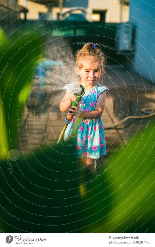 Happy 2-3 year old girl with garden hose water the plants plants. baby wattering backyard family love child person summer kid nature sun animal grass happy
