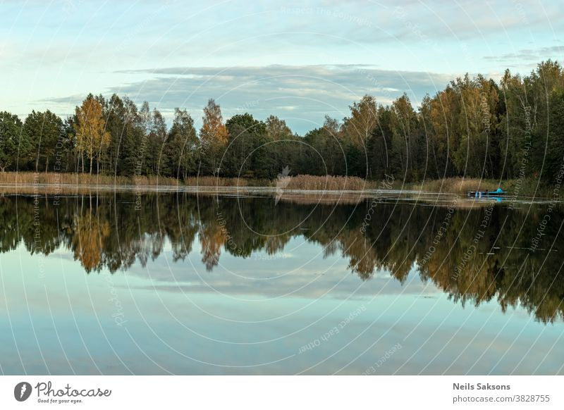 Colorful autumn landscape. Blue sky. Beautiful clouds. Colorful autumn evening in lake. Autumn forest reflected in water. Beautiful landscape with colorful forest.