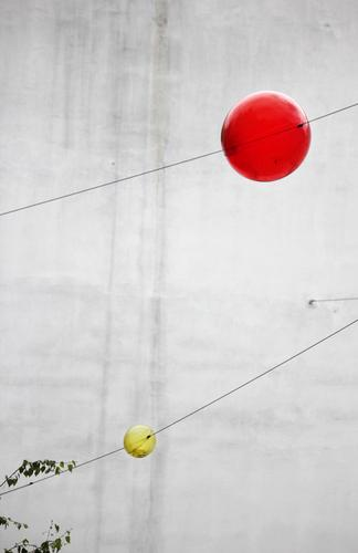 child amusement Wall (barrier) Wall (building) Glass ball Wire cable Hang Exceptional Round Yellow Gray Red Joy Relationship Design Idea Concentrate Ease