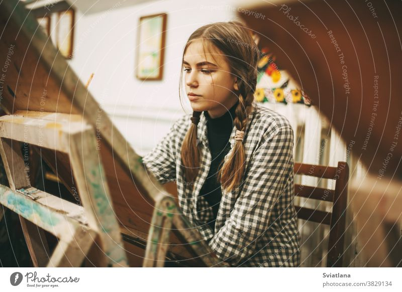 Beautiful teenage girl at art school painting on easel, creativity concept, art studio woman palette brush people female beautiful happy painter education young