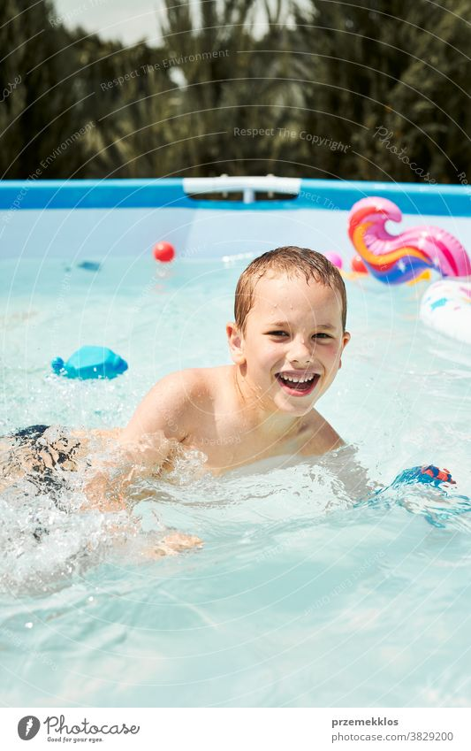 Portrait of happy smiling boy playing in a pool having fun on a summer sunny day authentic backyard childhood children family garden happiness joy kid laughing