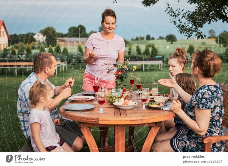 Family having a meal during summer picnic outdoor dinner in a home garden feast food man together woman child barbecue table eating gathering people lifestyle