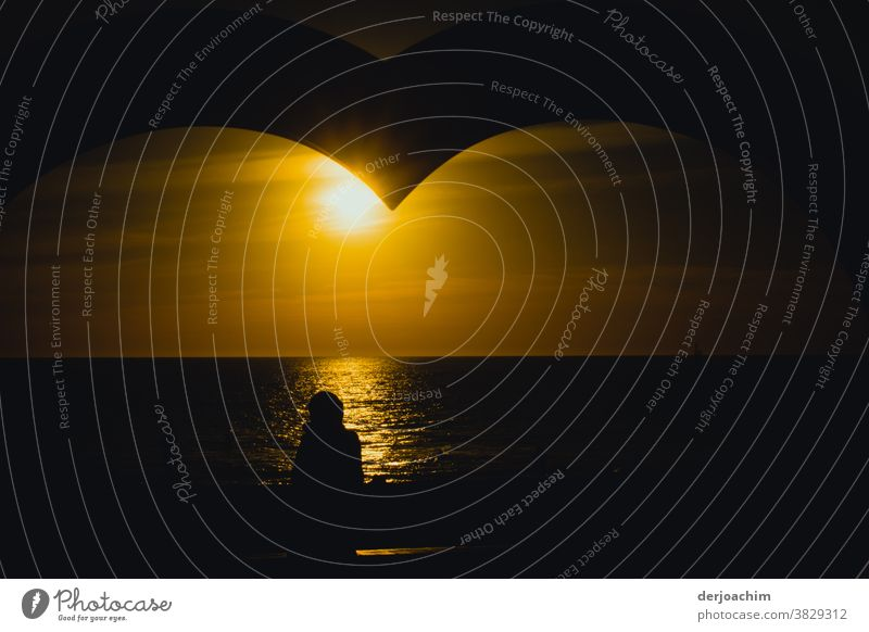 Evening sun with heart, waiting for the sunset at the sea. The structure of a heart in the upper picture is still visible. A shadow of a person standing on the shore is visible.