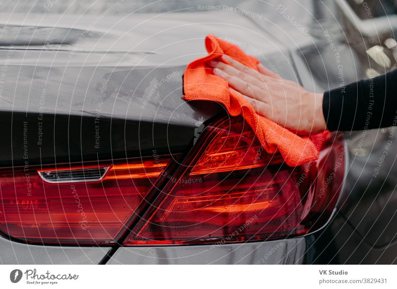 Cleaning auto concept. Mans hand wiping car hood with microfiber cloth. Unrecognizable man polishes vehicle. Detailing or valeting arm automobile care clean