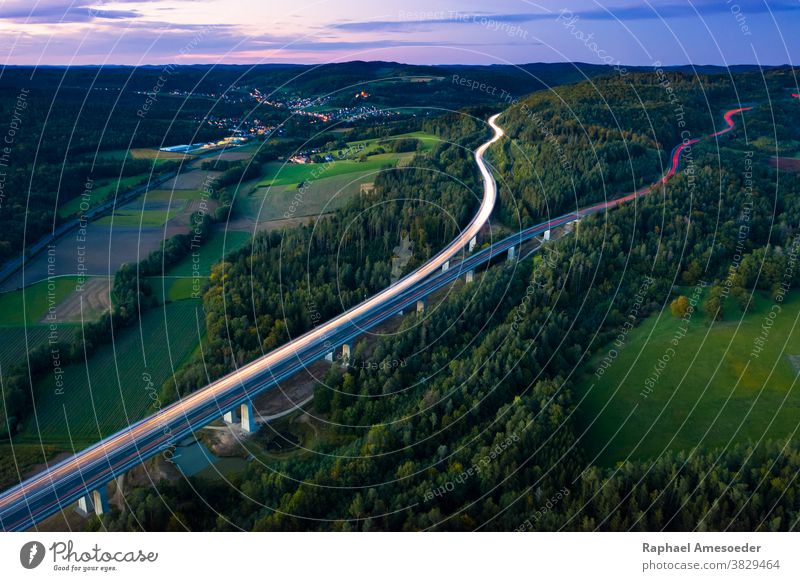 Aerial view of highway splitting aound forest hill on autumn evening, long exposure above aerial agriculture architecture blue bridge clouds countryside europe