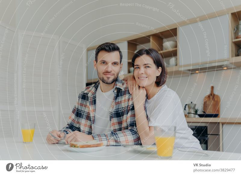 Positive brunette woman leans at shoulder of her husband, pose together at kitchen, enjoy delicious breakfast, have happy mood, look directly at camera, have good relationships. Family concept