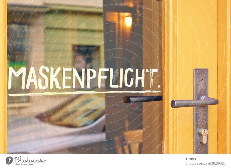 """""""MASKENPFLICHT"""" is handwritten in white on the glass of a yellow shop door Mask obligation business Load Pane Clue Front door Glass door protective measure"""