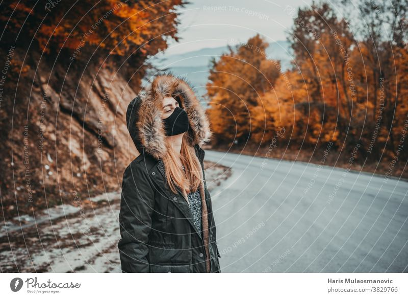 woman with mask and closed eyes standing  on mountain road autumn autumn colors autumn leaves autumn vibes background beautiful beautiful woman caucasian
