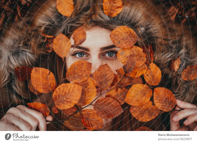 woman holding autumn leaves as natural face mask autumn colors autumn vibes background beautiful beautiful woman caucasian celebration clean close up clothes