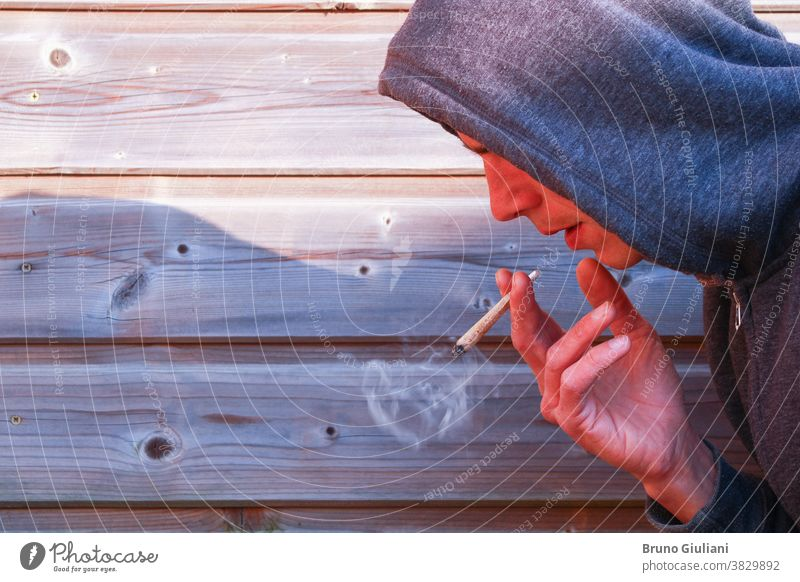 Boy with a rolled cigarette with a wrinkled hand. Man alone smoking marijuana against a wooden picket fence. drug joint portrait cannabis addiction adult weed