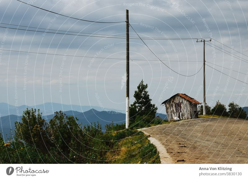 Panorama Street Wooden hut hillside Mountain Landscape Exterior shot Deserted Vacation & Travel Colour photo Sky Nature power line cloudy Clouds cloudy sky Peak
