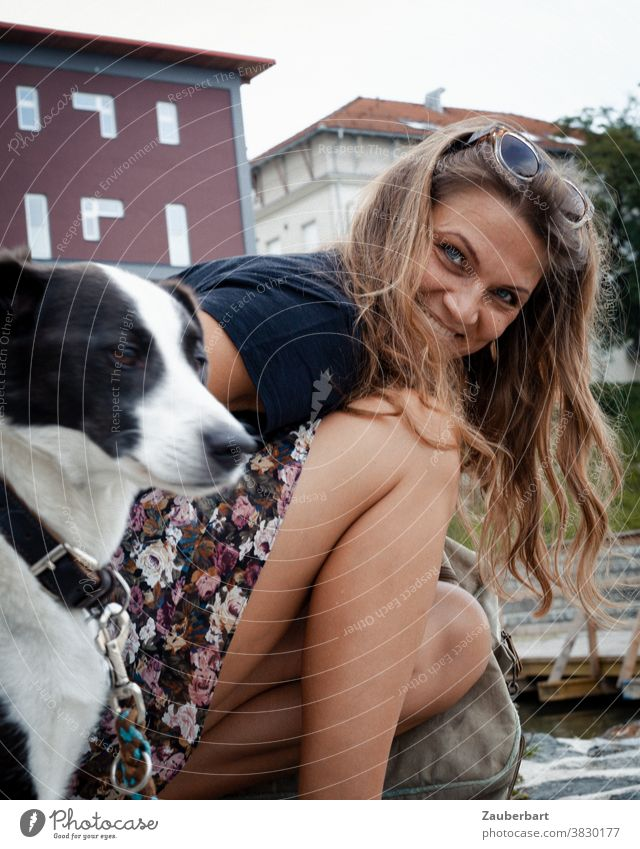 Beautiful woman kneels beside her dog and smiles Woman pretty cheerful Smiling rays Dog portrait Feminine Adults Brunette hair Kneel