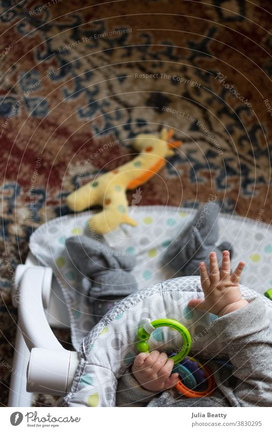 Baby seated with toys on orange rug; reaching towards giraffe toy baby infant child 0 - 12 months infancy childhood plastic rings booties drop object permanence