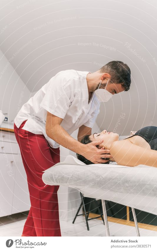 Male therapist doing procedures with client in clinic physiotherapy treat doctor patient table medical health care professional neck gown mask healthy