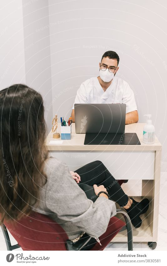 Serious doctor with patient in medical room in hospital man work laptop mask clinic typing physician male busy occupation specialist device using table gadget