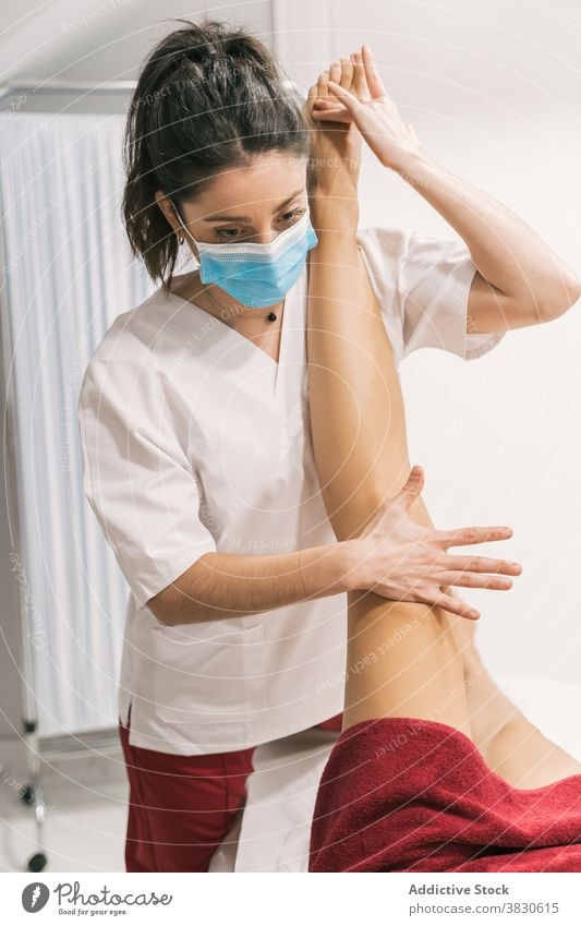 Physiotherapist stretching leg of patient in medical room rehabilitation physiotherapy help treat mask health care professional doctor procedure contemporary