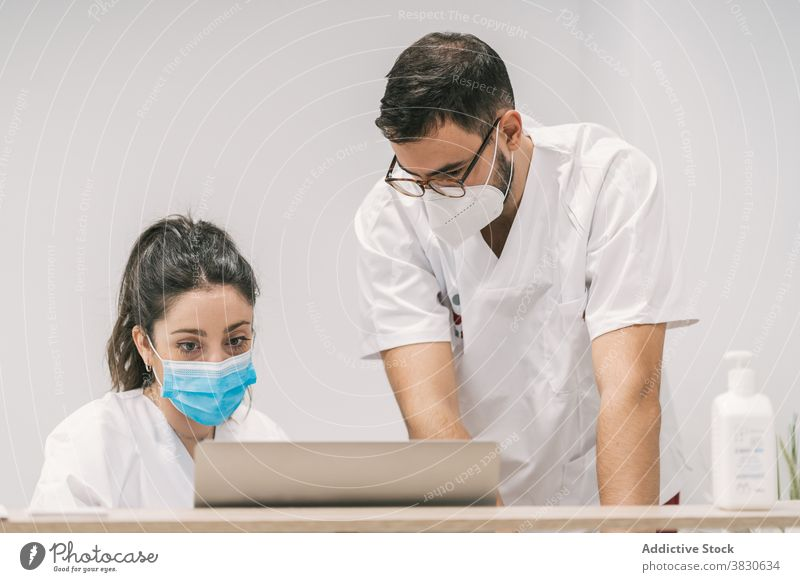 Busy doctors working on laptop in hospital clinic together colleague mask professional job occupation netbook device health care computer concentrate staff