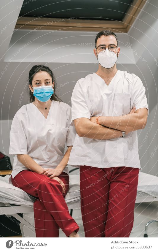 Smiling doctors in uniform and mask looking at camera medic hospital staff cheerful smile occupation specialist professional medical stand service medicine