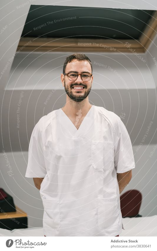 Cheerful doctor in uniform in medical room white gown man cheerful staff clinic office male medicine job modern specialist smile treat professional positive