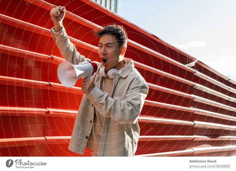 Emotional Asian man shouting in loudspeaker and raising fist scream megaphone rebel revolutino emotional overwhelmed agitate fist up provocation gesture
