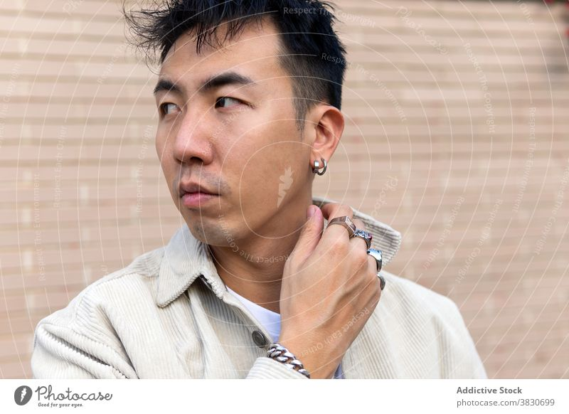 Pondering Asian man standing with eyes closed against brick wall ponder calm unemotional touch lapel thoughtful serious masonry pensive think casual contemplate
