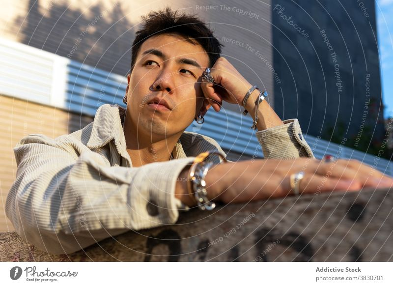 Contemplative Asian man leaning on hand against brick building thoughtful pensive lean on hand rest calm contemplate phlegmatic daydream street unemotional