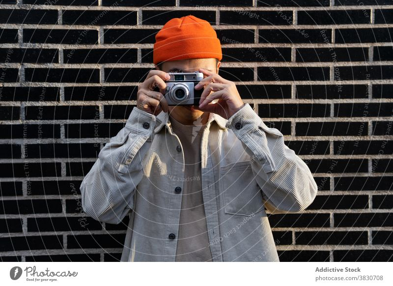 Man taking photos standing on brick wall man take photo photography device memory photo camera photographer gadget street moment hipster male equipment lens