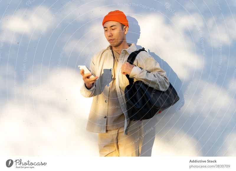 Asian man with travel bag using smartphone against white wall concentrate browsing cellphone focus surfing gadget modern young casual mobile calm device baggage