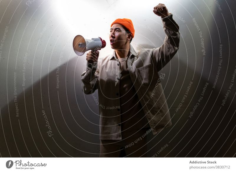 Expressive man shouting in megaphone against gray wall scream overwhelmed expressive loudspeaker darkness emotion exclaim voice yell call confident modern