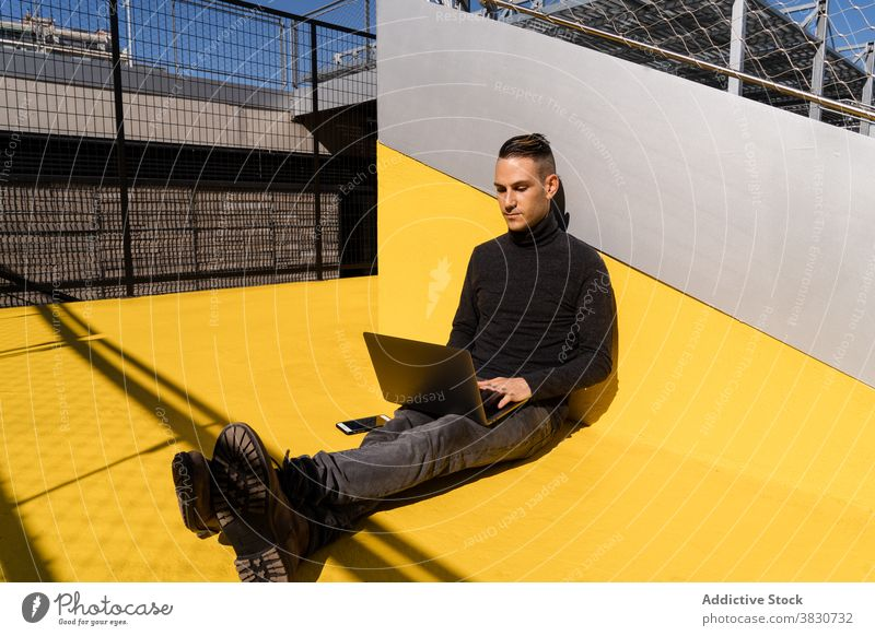 Young male surfing laptop while working outside man typing startup using focus concentrate serious busy browsing online connection job watch internet sunny park
